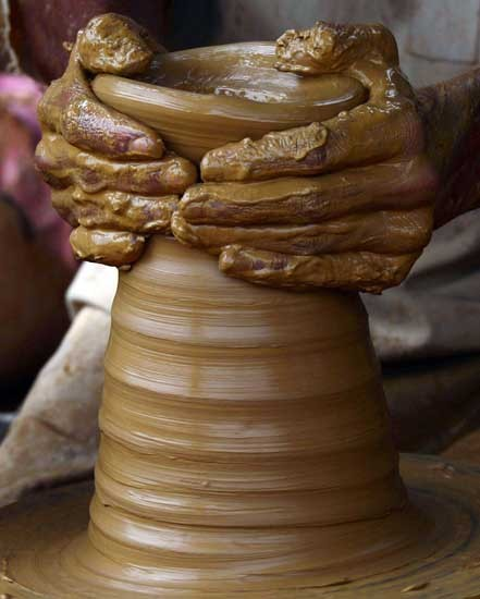 A Pakistani artisan makes traditional pottery items at a workshop on the outskirts of Karachi on July 9, 2013. Hundreds of Pakistani potters, locally known as Kumhars, manufacture earthen pots in rural and suburban areas which are cheaper and mostly used for cooking and as decorated pieces in rural areas in the sub-continent. AFP PHOTO / RIZWAN TABASSUM