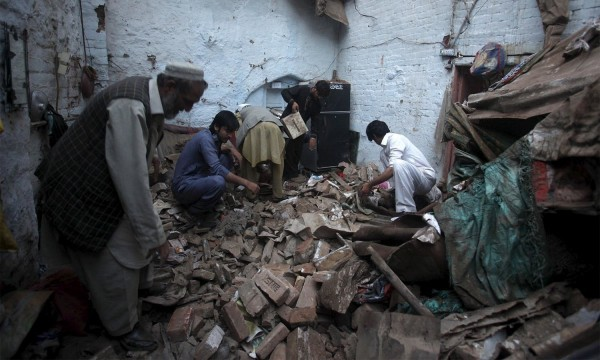 Residents search for belongings in the rubbles of a house after it was damaged by an earthquake in Peshawar, Pakistan, October 26, 2015. A major earthquake struck the remote Afghan northeast on Monday, killing at least 135 people in Afghanistan and nearby northern Pakistan and sending shock waves as far as New Delhi, officials said. REUTERS/FAYAZ AZIZ