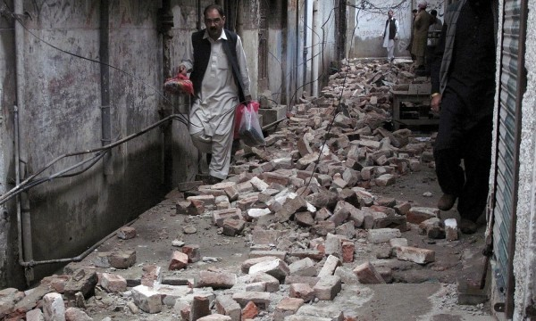 A man with his belongings walks past the rubble of a house after it was damaged by an earthquake in Mingora, Swat, Pakistan October 26, 2015. A powerful earthquake struck a remote area of northeastern Afghanistan on Monday, shaking the capital Kabul, as shockwaves were felt in northern India and in Pakistan's capital, where hundreds of people ran out of buildings as the ground rolled beneath them. REUTERS/Hazrat Ali Bacha