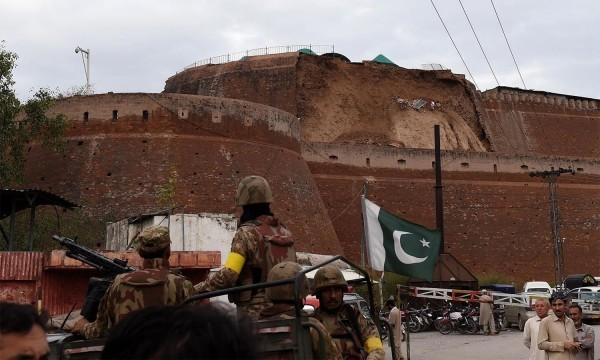 Pakistani paramilitary soldiers observe the damaged wall of a fort used by security forces after an earthquake in Peshawar on October 26, 2015. At least 17 people including eight children were killed in Pakistan when a 7.5 magnitude quake struck in Afghanistan October 26, officials said. AFP PHOTO / A MAJEED
