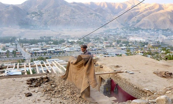 A man clears rubbles from the roof of his house after an earthquake, in Fayzabad capital of Badakhshan province, Afghanistan October 26, 2015. A powerful earthquake struck a remote area of northeastern Afghanistan on Monday, shaking the capital Kabul, as shockwaves were felt in northern India and in Pakistan's capital, where hundreds of people ran out of buildings as the ground rolled beneath them. REUTERS/Stringer          EDITORIAL USE ONLY. NO RESALES. NO ARCHIVE