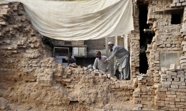 Residents clear the rubble of a house after it was damaged by an earthquake in Peshawar, Pakistan October 26, 2015. A powerful earthquake struck a remote area of northeastern Afghanistan on Monday, shaking the capital Kabul, as shockwaves were felt in northern India and in Pakistan's capital, where hundreds of people ran out of buildings as the ground rolled beneath them. REUTERS/Khuram Parvez