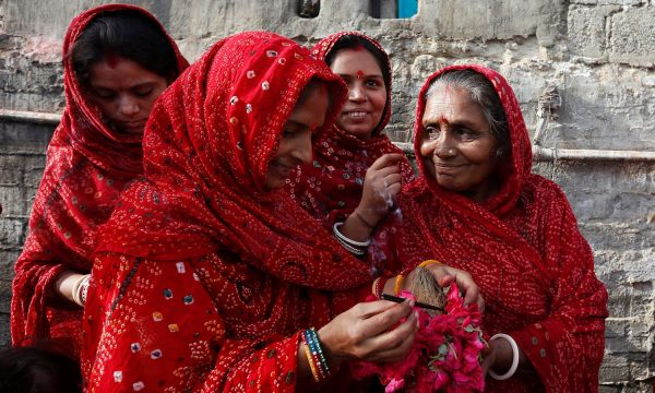 Women light incense while holding roses and a coconut to perform ritual on the occasion of Raksha Bandhan festival at the Shri Laxmi Narayan temple in Karachi,